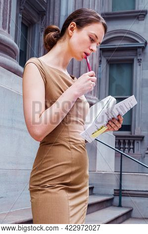 Working Outside. Dressing Formally And A Pen Touching Lips, A Professional Businesswoman Is Working