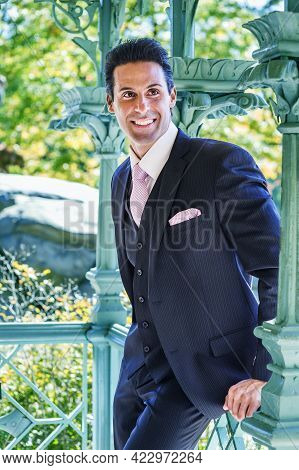 Waiting For You. A Middle-aged Handsome Man, Wearing A Three Pieces Dark Blue Suit, A Patterned Pink