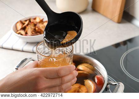 Woman Pouring Compot Into Glass Near Stove, Closeup