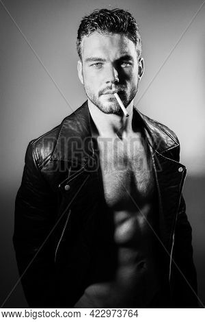 Portrait Of Handsome Young Man With Open Leather Jacket Revealing Sixpack Abs With Cigarette In His