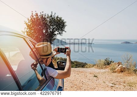 Man Taking Picture With Smarphone From Open Window Of A Car Stopped Roadside