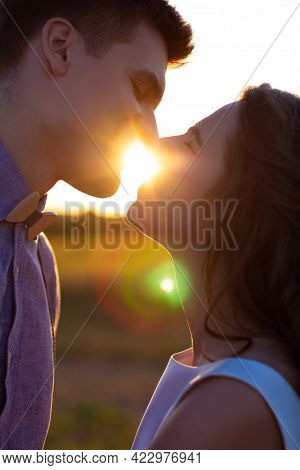 Silhouette Of Happy Couple In Love At Sunset In Green Grass Field. Man Stands In Front Of Young Woma
