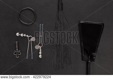 Kinky Sex Toys On Black Leather Background, Flat Lay.