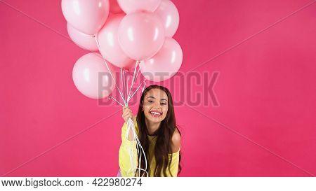 Joyful Young Adult Woman In Yellow Sweatshirt Holding Balloons Isolated On Pink