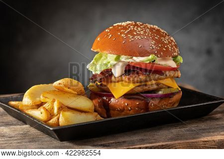 Yummy juicy hamburger with double cutlet, french fries in a metal bowl on a wooden table. Hamburger and french fries. Fast food concept.