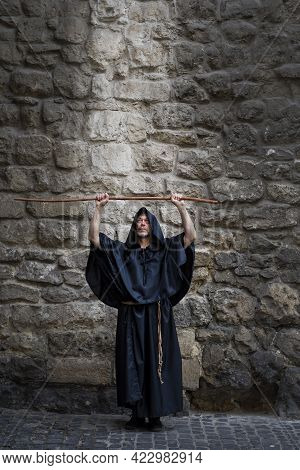 The Monk Holds His Staff High Against The Textured Stone Wall, The Light Descending On Him From Abov