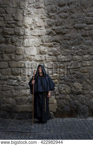 A Monk With A Staff At A Textured Stone Wall, Light Falling On Him From Above. Concept: Prayer And M