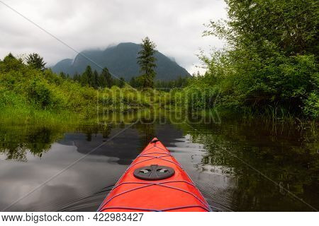 Adventure Concept Kayaking In Red Kayak Surrounded By Canadian Mountain Landscape. Taken In Widgeon
