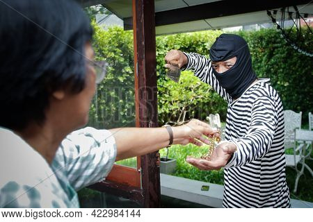 Male Thief Wearing Black Mask Carrying Large Knives Into The House Of An Elderly Woman To Rob And Fo