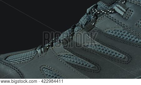 Closeup To The Upper Part Of A Blue Gray Fabric And Leather Sports Shoe On A Black Background