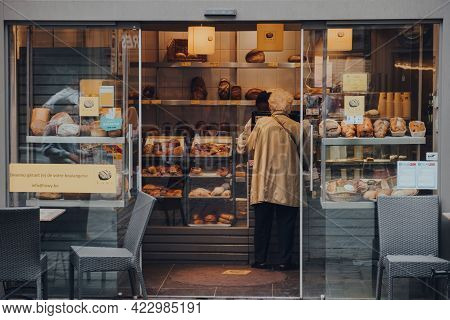Brussels, Belgium - August 17, 2019: View Through Open Doors Of A Woman Buying Bread In Lowy Bakery