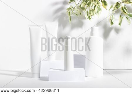 A Set Of White Cosmetic Jars On Square Stands With Shadows. Toothpaste, Face And Body Cream, Hair Sh