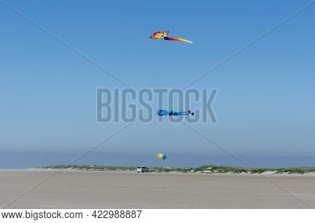 Huge Kites Flying In A Lbue Sky On The Beach With A Van Life Bus Parked Underneath