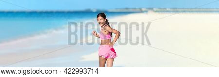 Happy running fitness girl looking back smiling on beach run jogging active healthy lifestyle. Asian woman athlete exercising cardio working out in summer outdoors.
