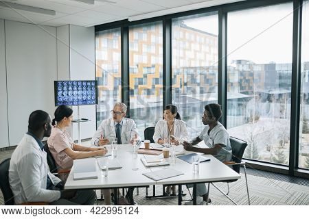 Wide Angle View At Doctors Sitting At Meeting Table In Conference Room During Medical Council, Copy