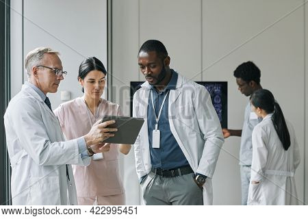 Waist Up Portrait Of Diverse Group Of Doctors Looking At Digital Tablet During Council Or Conference