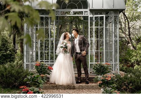 Full Length View Of Young Newlyweds In Medical Masks Kissing Near Alcove In Park