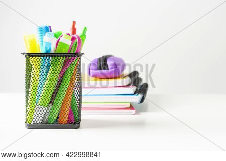 Several Markers, Colored Pens, Scissors In A Metal Basket Next To Several Colored Notebooks On A Whi