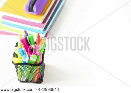 Group Of Markers, Colored Pens, Scissors In A Metal Basket Next To Several Colored Notebooks On A Wh