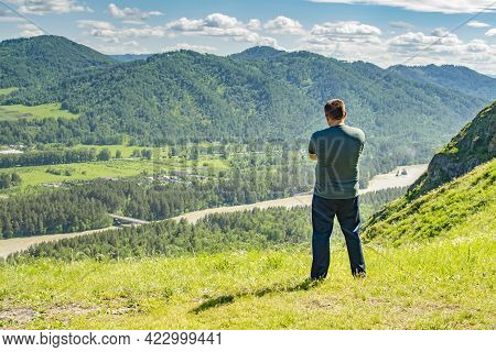 A Lonely People, A Man Stands On The Top Of A Mountain And Looks Thoughtfully, Admiring The Natural