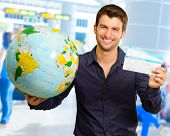 Young Man Holding Globe And Boarding Pass, Indoors poster