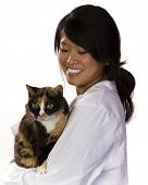 Attractive vet with a calico cat in her arms poster