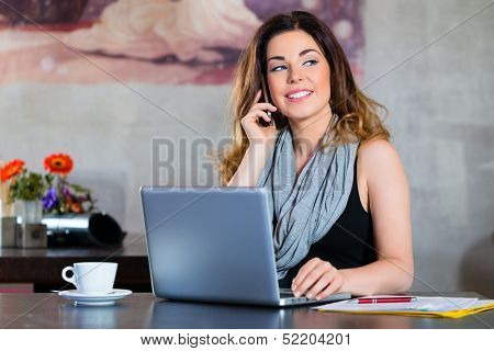 Young woman in a cafe or restaurant, she using the wifi hotspot with laptop computer for working
