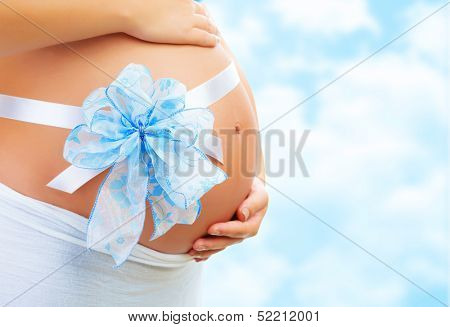 Closeup on belly of expectant woman with cute blue ribbon bow on blue cloudy sky background, it's a boy, young family, new life concept