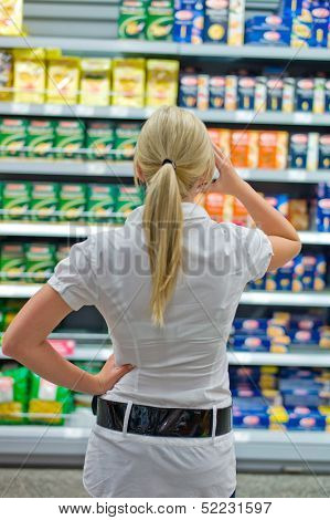 a young woman stands in front of a desperate shelf in the supermarket. excess supply of goods.