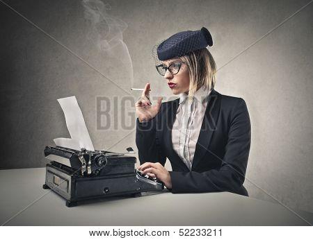 beautiful blonde woman writes with a typewriter