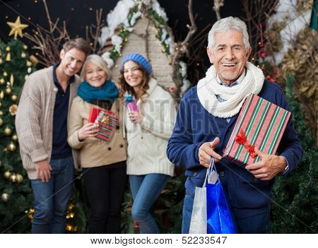 Portrait of cheerful man holding Christmas presents and shopping bags with family standing in background at store