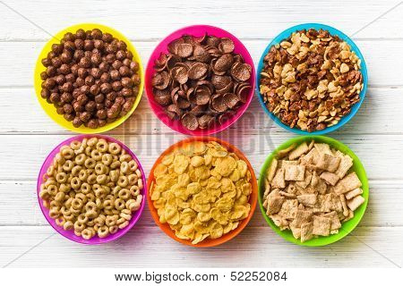 top view of various kids cereals in colorful bowls on wooden table