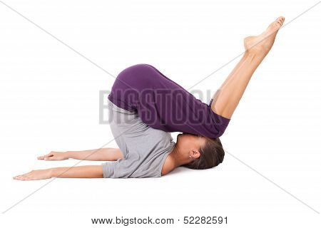 Young Woman Doing Yoga Exercise Halasana (plow Pose)