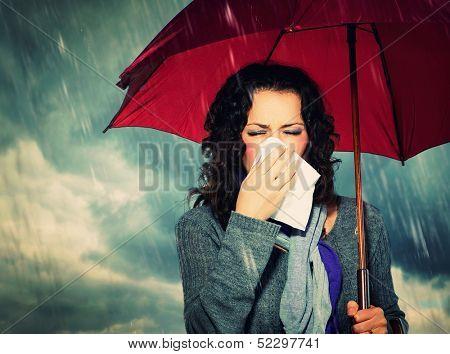 Estornudo mujer con paraguas sobre fondo de lluvia de otoño. Mujer enferma al aire libre. Gripe. Chica resfriado