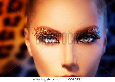 Beauty Fashion Model Girl with Holiday Leopard Makeup. Golden Wild Cat Eyes Make-up Eyeshadow. Beautiful Woman Face with Perfect skin. Animal Make up poster