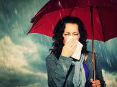 Sneezing Woman with Umbrella over Autumn Rain Background. Sick Woman outdoors. Flu. Girl Caught Cold. Sneezing into Tissue. Headache. Virus. Bad Weather  poster