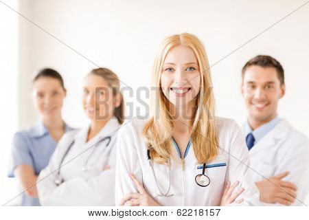 healthcare and medicine concept - attractive female doctor or nurse in front of medical group in hospital poster