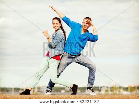 summer holidays, teenage and dancing concept - couple of teenagers dancing outside