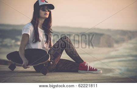 Beautiful fashion skater girl posing with  a skate board poster