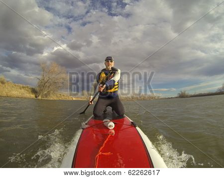 mature male paddler in wetsuit and life jacket enjoying workout on a stand up paddleboard (SUP), windy lake in one of nature areas in Fort Collins, Colorado,  distorted wide angle view