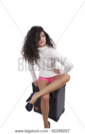 Confident young female fashion model posing on a speaker