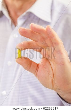 Senior adult man holds medicine capsule