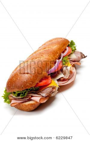 A submarine sandwich with ham turkey roast beef bacon lettuce tomato cheese and onion on a white background poster