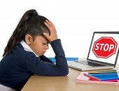 hispanic sweet little girl crying and suffering internet bullying and abuse at school sitting at desk with computer and stop sign poster