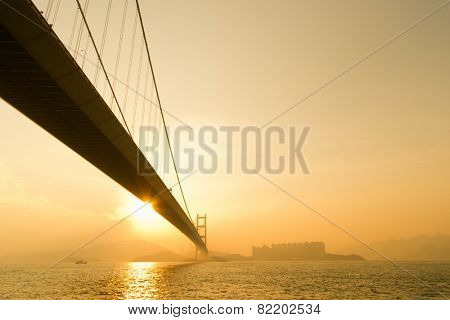 Sunset scenery of Tsing Ma Bridge with sun light and flare in Hong Kong, Asia.