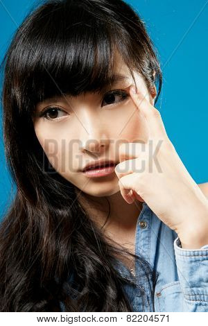 Attractive Asian beauty thinking, closeup portrait on studio blue background.