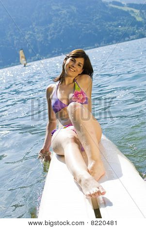 Girl Relaxing On Surfboard