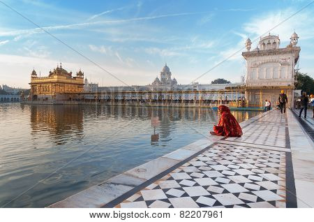 Woman In A Red Saree Sits And Pray In Golden Temple In The Early Morning. Amritsar. India