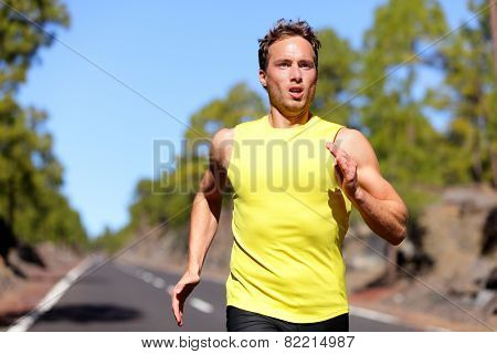 Running man sprinting for success on run. Male athlete runner training at fast speed. Muscular fit sport model sprinter exercising sprint on forest road. Caucasian fitness model in his 20s. poster