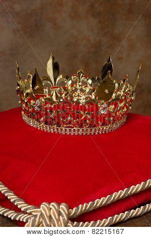 Medieval golden king's crown on red velvet pillow